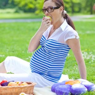 Una mujer embarazada, comiendo una manzana