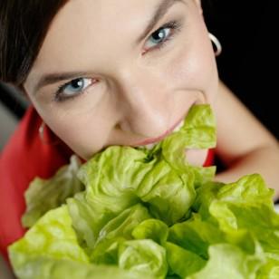 Una mujer. comiendo hojas de lechuga