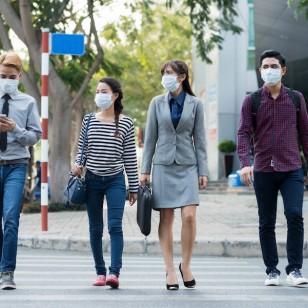 Varias personas, con mascarilla por la contaminación