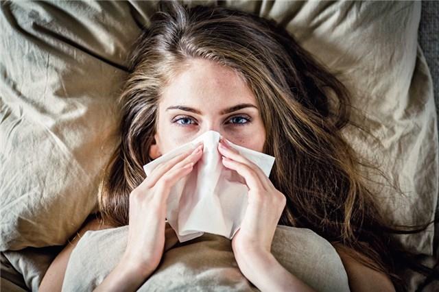 Una mujer en la cama con un resfriado