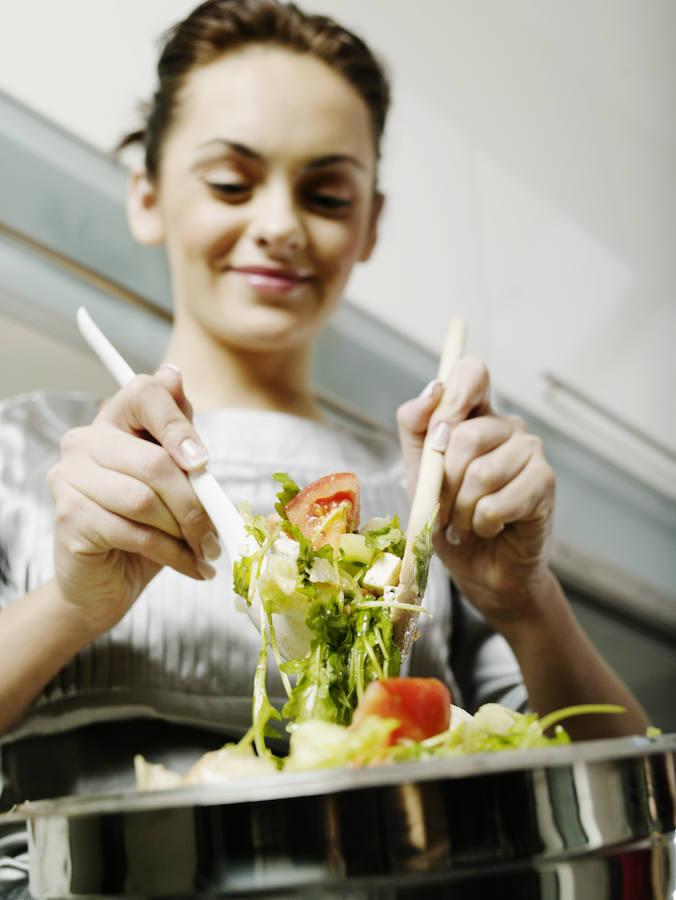 Una mujer se sirve ensalada