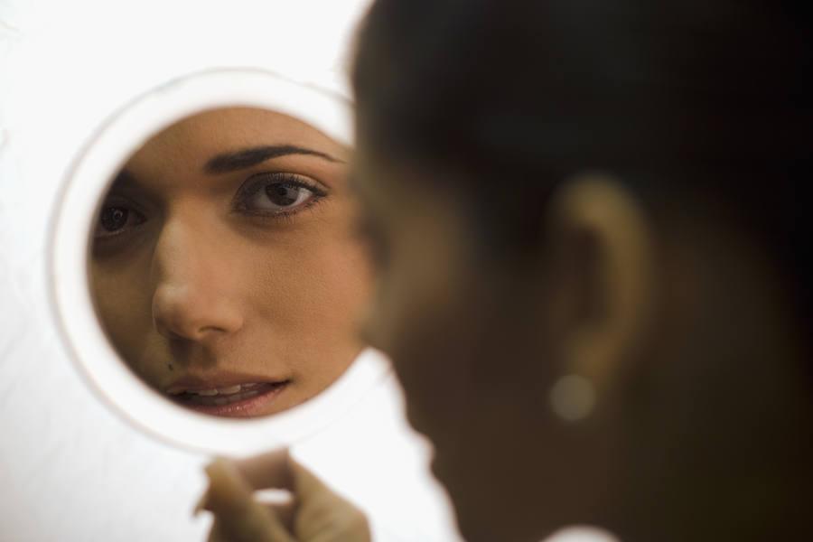 Una mujer se mira en el espejo