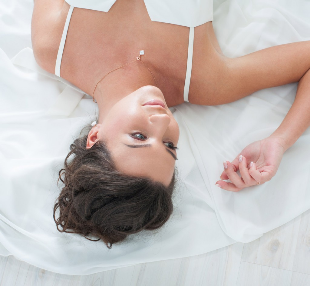 A beautiful Girl  is in a Wedding Dress lying  on the floor  in studio