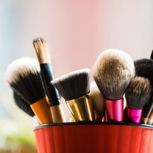 professional brush for fashionable makeup or cosmetic in pink cup on blurred background, fashion and beauty, visage and design