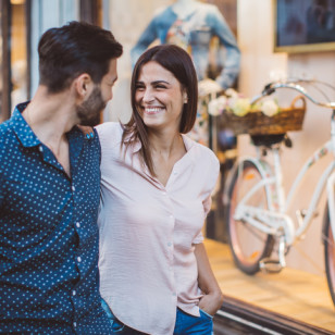 Couple walking by shop's window. Enjoying in shopping together