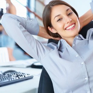 Portrait of cute business woman sitting in office and relaxing with hands behind head