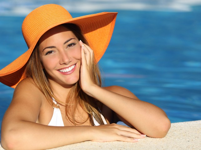 Girl on holidays with a perfect white smile bathing in a pool on vacations