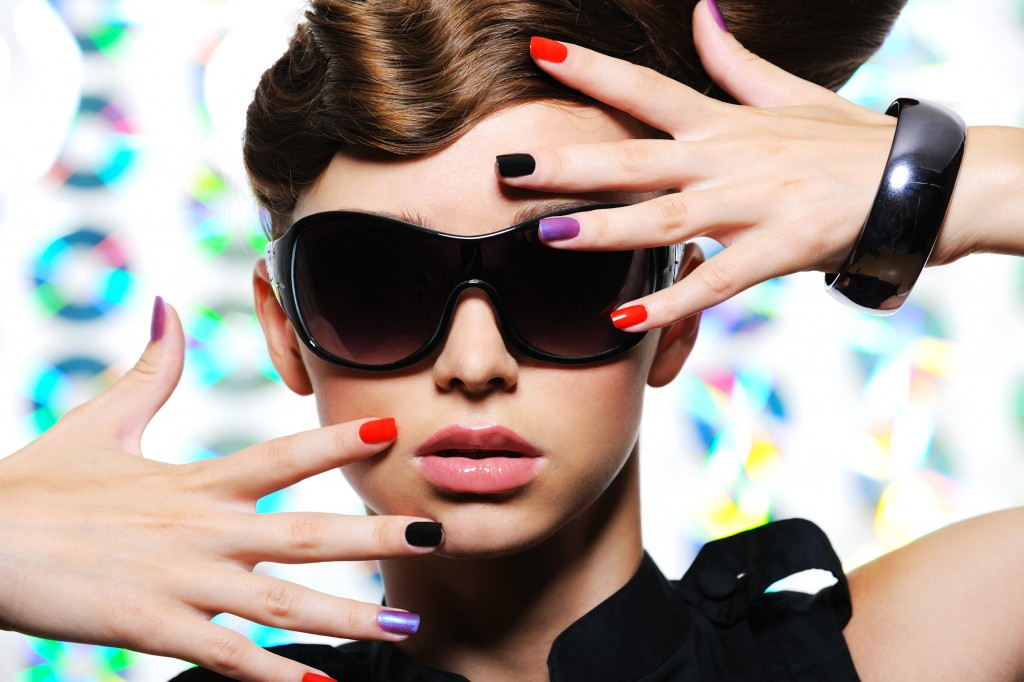 adult woman with fashion multicolored manicure and female stylish sunglasses - close-up